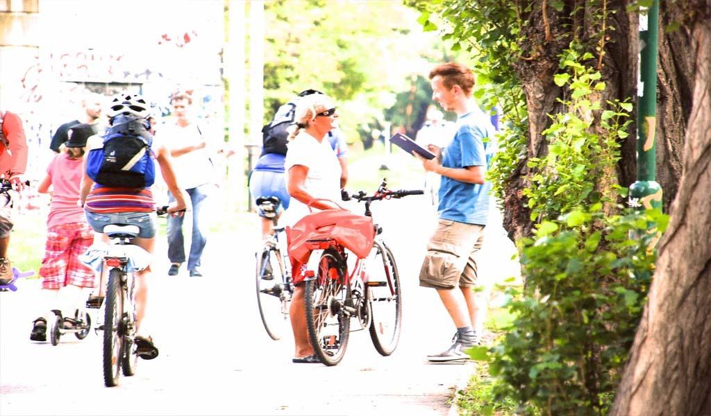 Ein Mann auf einem Fahrrad im freien spricht mit einem jungen Mann der ein Tablet in der Hand hält
